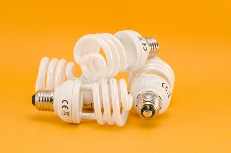 Drei moderne energiesparende elektrische Birnen auf gelbem Hintergrund stockbild