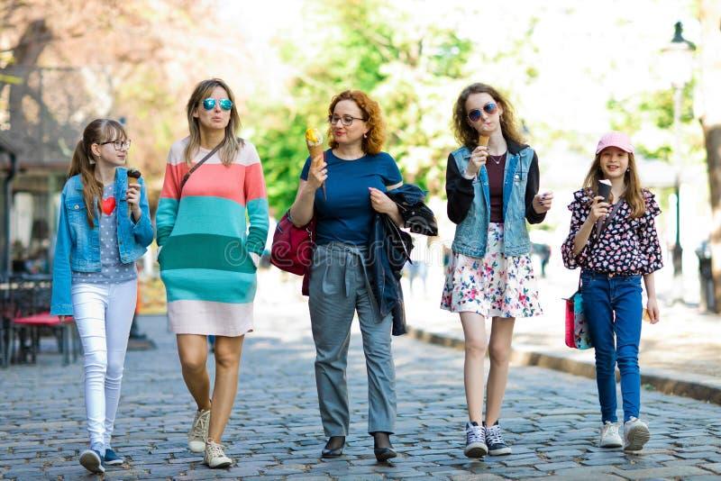 Gruppe Modemädchen, die durch im Stadtzentrum gelegenes - Eis cre haben gehen stockfotografie