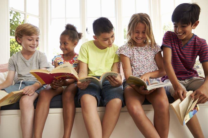 Gruppe multikulturelle Kinder, die auf Fensterplatz lesen lizenzfreie stockfotos