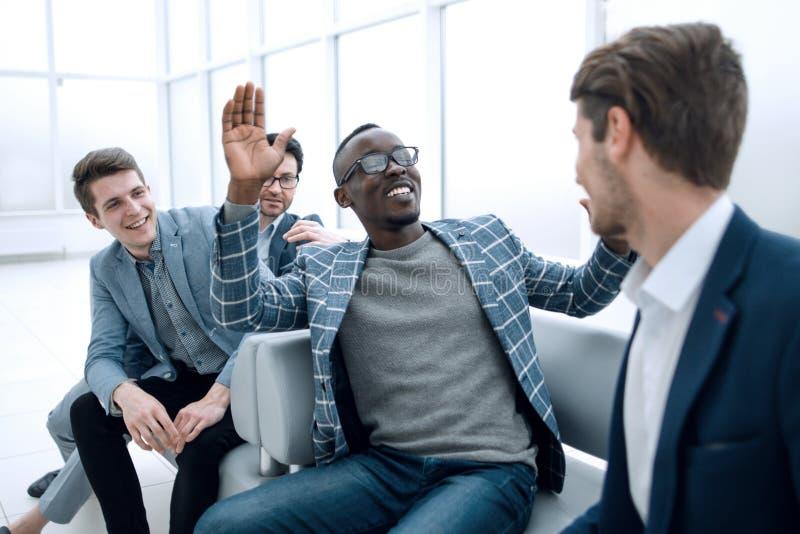 Gruppe nette Geschäftsleute, die in der Lobby des Büros sitzen stockfoto