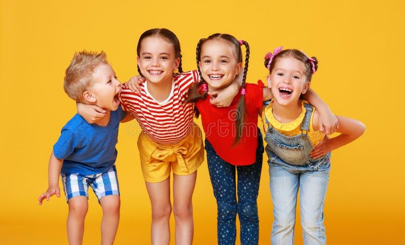 Gruppe nette gl?ckliche Kinder auf farbigem gelbem Hintergrund stockfotografie