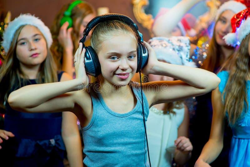 Gruppe nette junge Mädchen, die Weihnachten feiern kopfhörer stockbilder