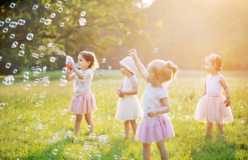 Gruppe nette Kinder, die Seifenblasen durchbrennen lizenzfreies stockbild