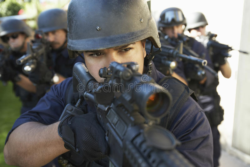Gruppe Polizeibeamten, die mit Gewehren zielen lizenzfreie stockbilder
