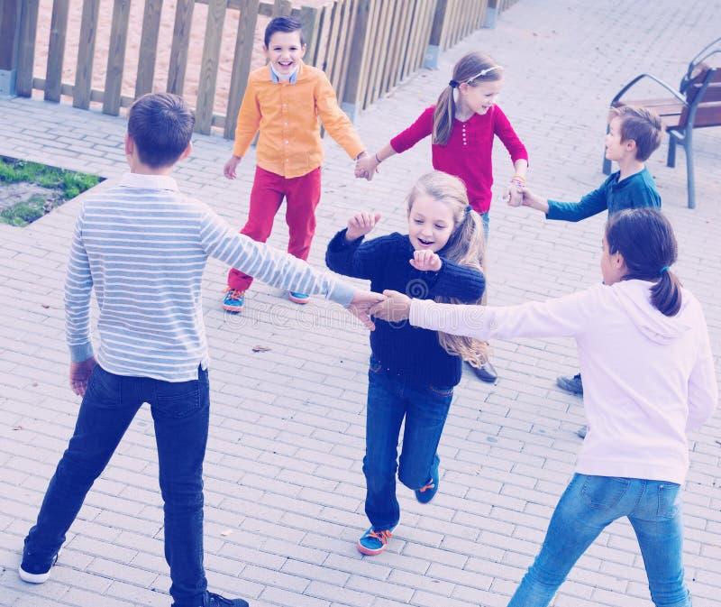 Gruppe positive Kinder, die roten Vagabunden spielen stockfotos
