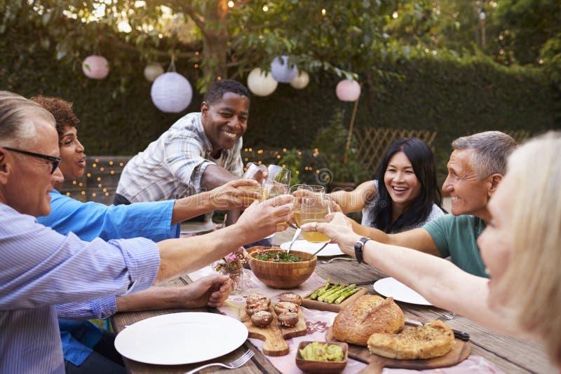 Gruppe reife Freunde, die Mahlzeit im Freien im Hinterhof genießen stockbild