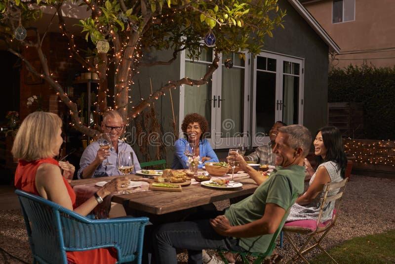 Gruppe reife Freunde, die Mahlzeit im Freien im Hinterhof genießen stockfotografie