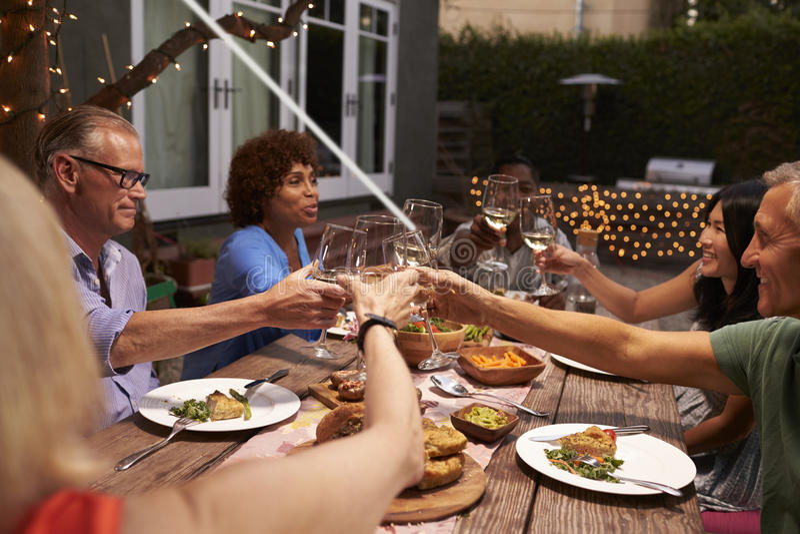 Gruppe reife Freunde, die Mahlzeit im Freien im Hinterhof genießen lizenzfreie stockfotografie