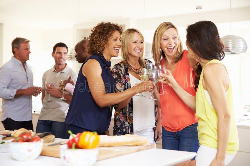 Gruppe reife Freunde, die zu Hause Abendessen genießen stockbild