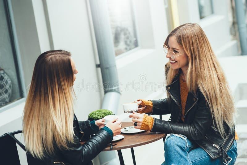 Gruppe schöne junge Mädchen, die einen Kaffee zusammen trinken lizenzfreie stockbilder