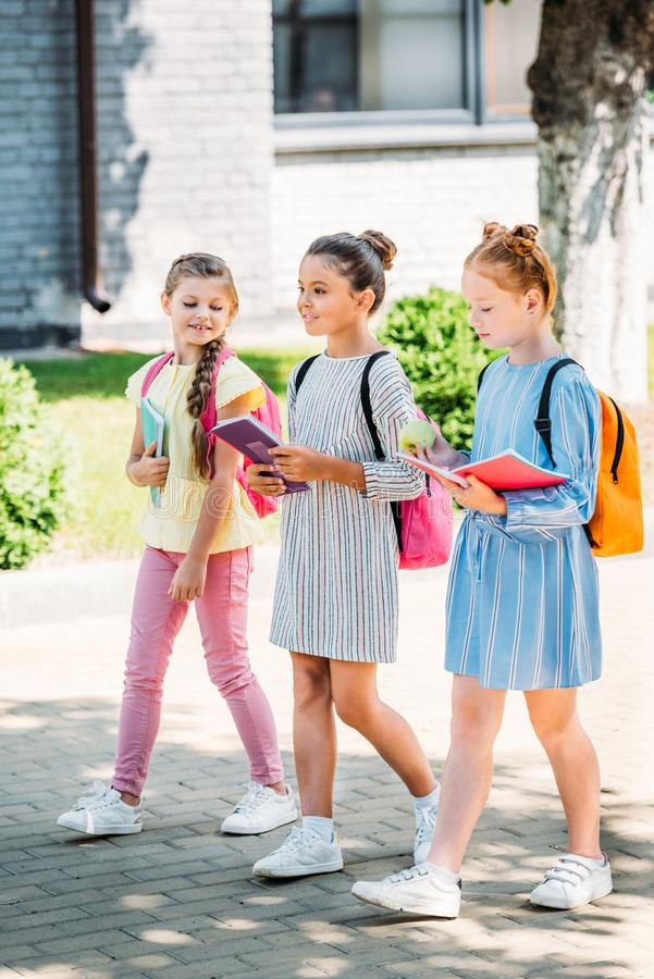 Gruppe schöne Schulmädchen mit Notizbüchern zusammen gehend stockbilder
