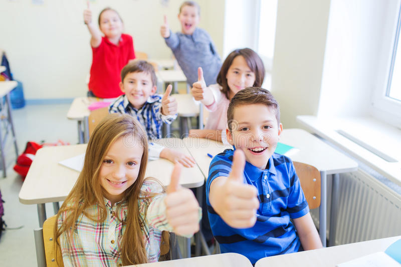 Gruppe Schulkinder, die sich Daumen zeigen lizenzfreie stockfotos