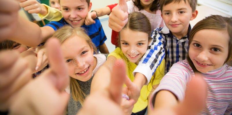 Gruppe Schulkinder, die sich Daumen zeigen stockbilder