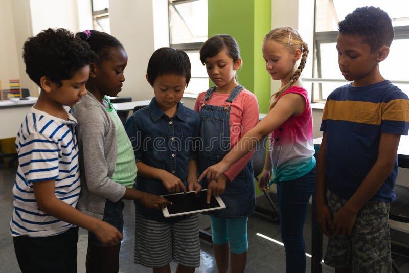 Gruppe Schulkinder, die zusammen auf digitaler Tablette im Klassenzimmer studieren stockbild