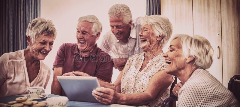 Gruppe Senioren, die digitale Tablette verwenden stockfotografie