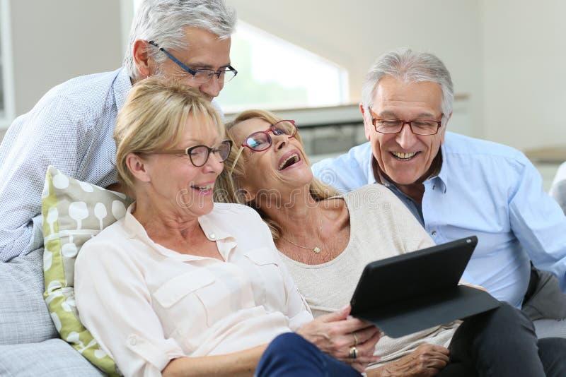 Gruppe Senioren, die Tablette lachen und verwenden lizenzfreies stockbild