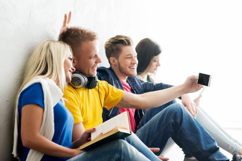 Gruppe Studenten auf einem Bruch Fokus auf einem Jungen, der Smartphone verwendet stockbild
