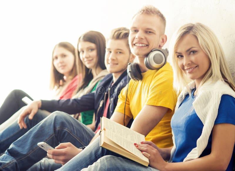Gruppe Studenten, die auf einem Bruch sich entspannen stockfoto