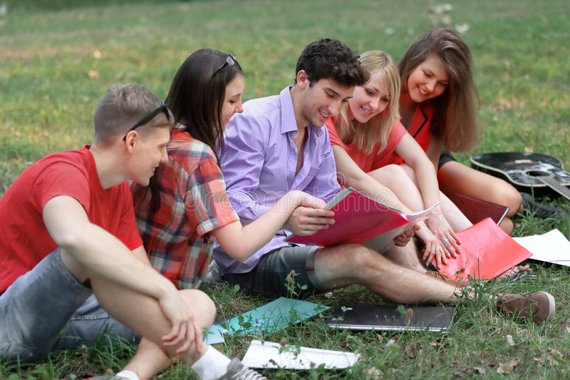 Gruppe Studenten, die auf Gras und Ablesenbuch im Park sitzen lizenzfreies stockbild