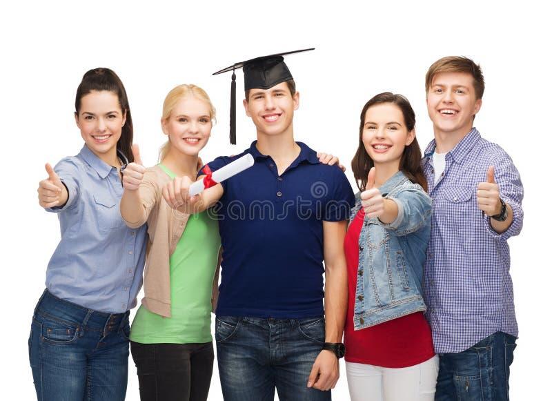 Gruppe Studenten mit dem Diplom, das sich Daumen zeigt lizenzfreie stockfotos
