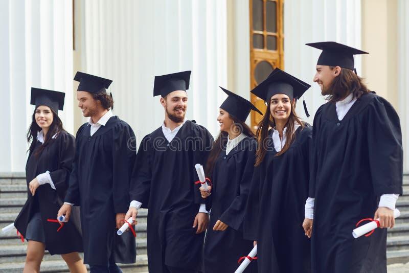 Gruppe Studentenabsolvent gegen die Universit?t gehen lizenzfreie stockbilder