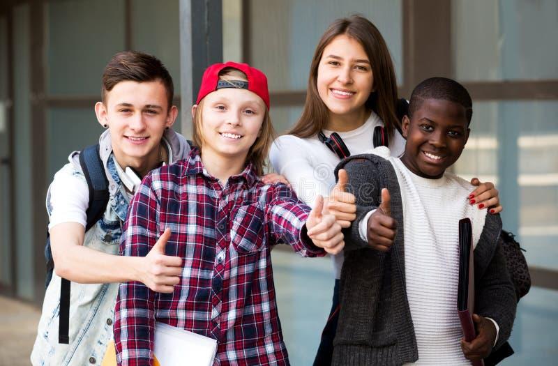 Gruppe Teenager, der äußere Schule aufwirft lizenzfreie stockfotos