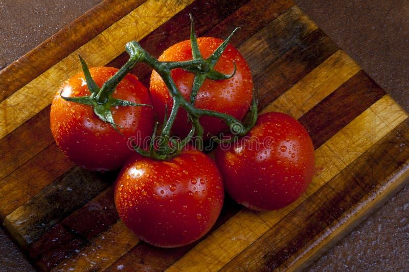 Gruppe Tomaten auf Schneidebrett stockfoto