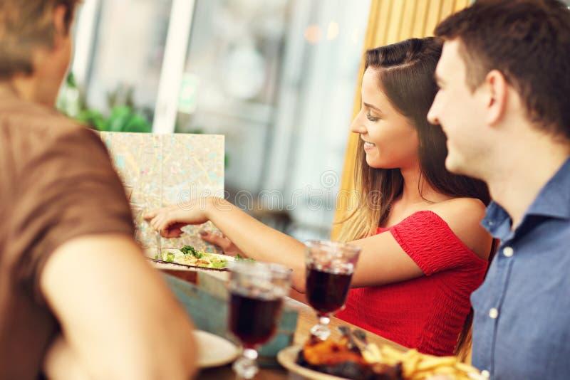 Gruppe Touristen, die auf Karte im Restaurant schauen lizenzfreies stockfoto