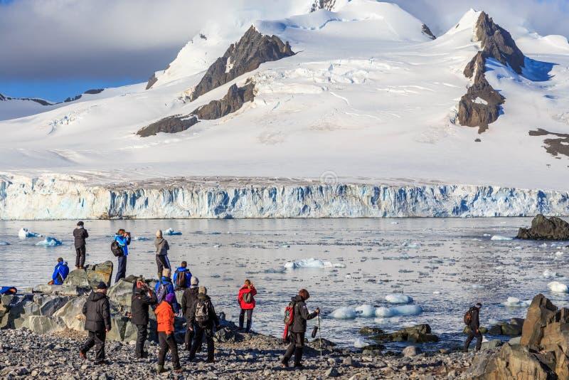 Gruppe Touristen, die den Gletscher auf das steinige Ufer betrachten stockbilder