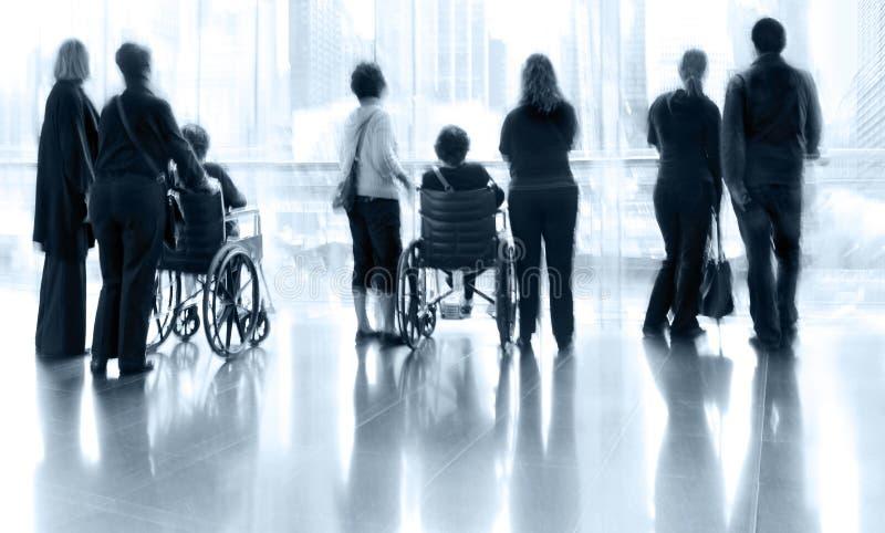 Gruppe und Behinderter im LobbyGeschäftszentrum stockfotografie