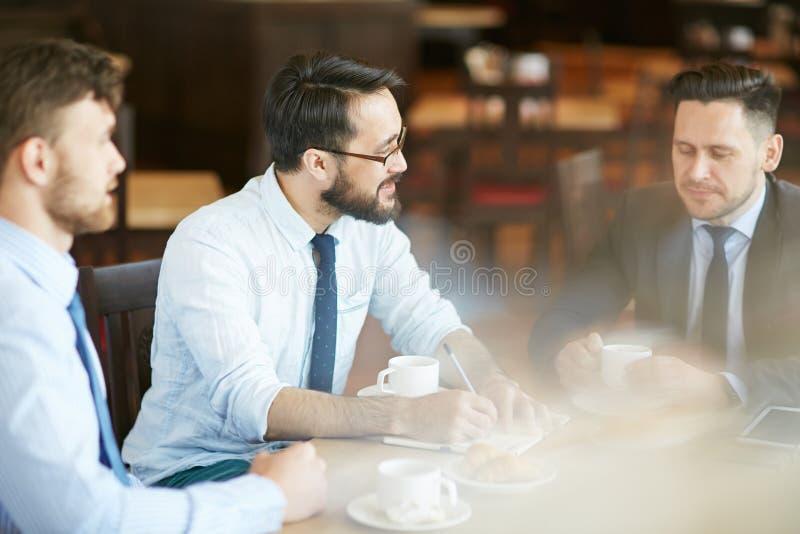 Gruppe Unternehmer, die über neues Projekt mit Partnern im Café gedanklich lösen stockbilder