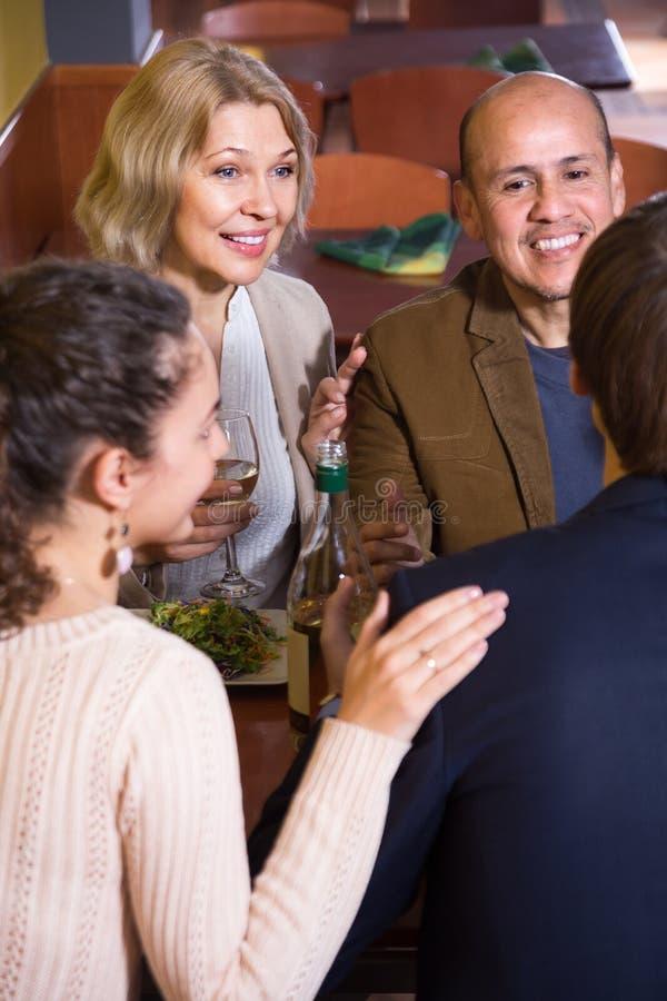 Gruppe verschiedene Altersfreunde, die Abendessen und Wein am restaur essen lizenzfreies stockbild