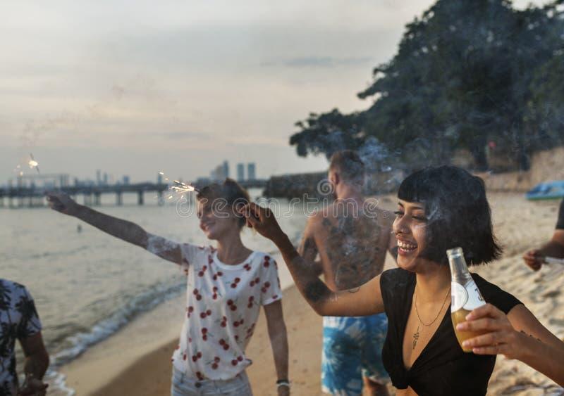 Gruppe verschiedene Freunde, die zusammen Wunderkerzen am Strand genießen stockbilder