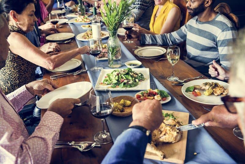 Gruppe verschiedene Freunde essen zusammen zu Abend stockfotografie