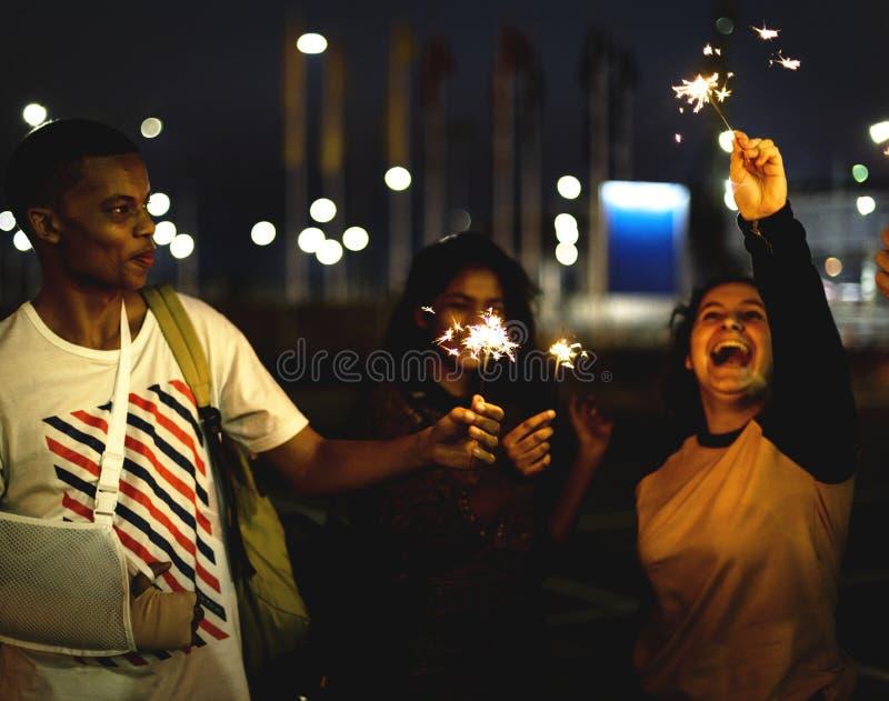 Gruppe verschiedene Jugendlichen, welche die Wunderkerzen genießen stockbilder