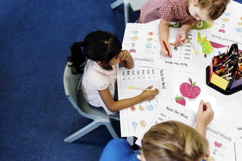 Gruppe verschiedene Kinder, die Arbeitsbuch in der Klasse färben stockfotos