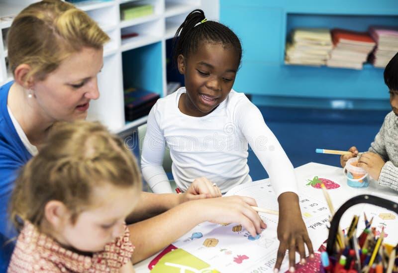 Gruppe verschiedene Kinder, die Arbeitsbuch in der Klasse färben stockfoto