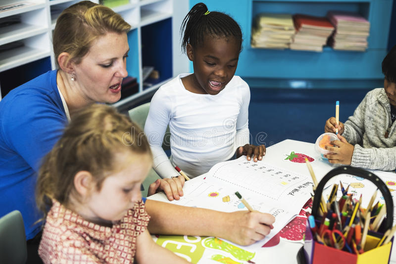 Gruppe verschiedene Kinder, die Arbeitsbuch in der Klasse färben lizenzfreie stockfotografie