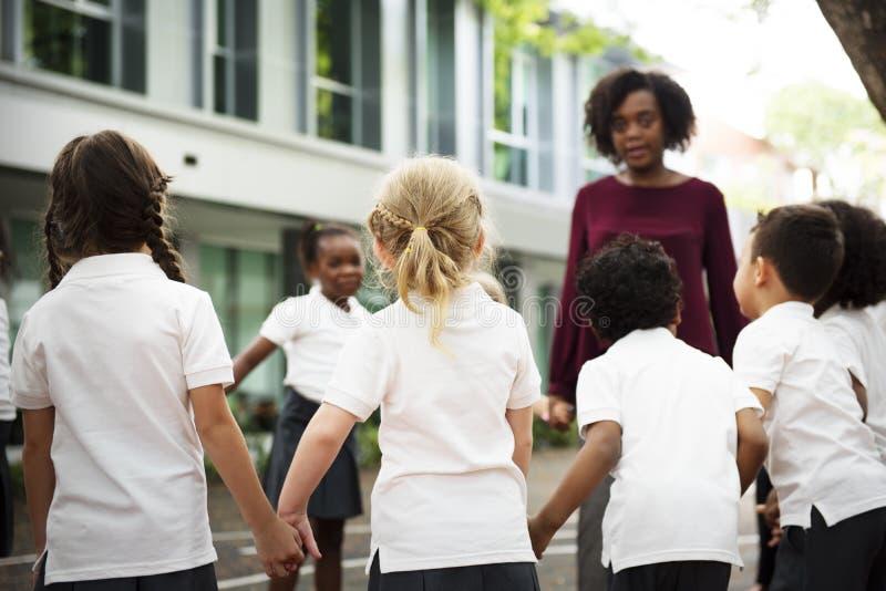 Gruppe verschiedene Kindergartenstudenten, die Händchenhalten zu stehen stockfotos