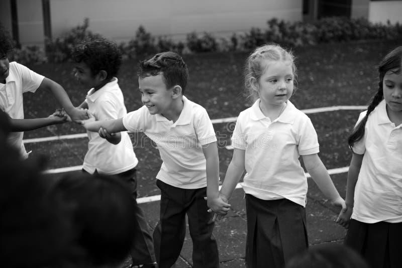 Gruppe verschiedene Kindergartenstudenten, die Händchenhalten zu stehen stockbilder
