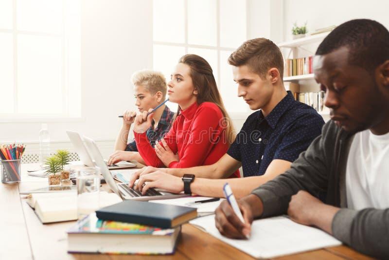 Gruppe verschiedene Studenten, die am Holztisch studieren lizenzfreie stockbilder