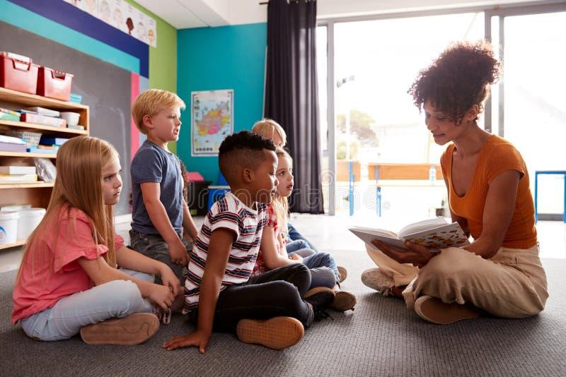 Gruppe Volksschule-Schüler, die auf Boden hörend auf weiblichen Lehrer Read Story sitzen lizenzfreie stockfotos