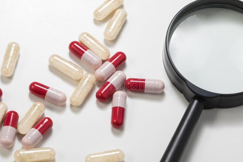 Gruppe von Antibiotika und von probiotics Kapsel mit Vergrößerungs-gla lizenzfreie stockbilder