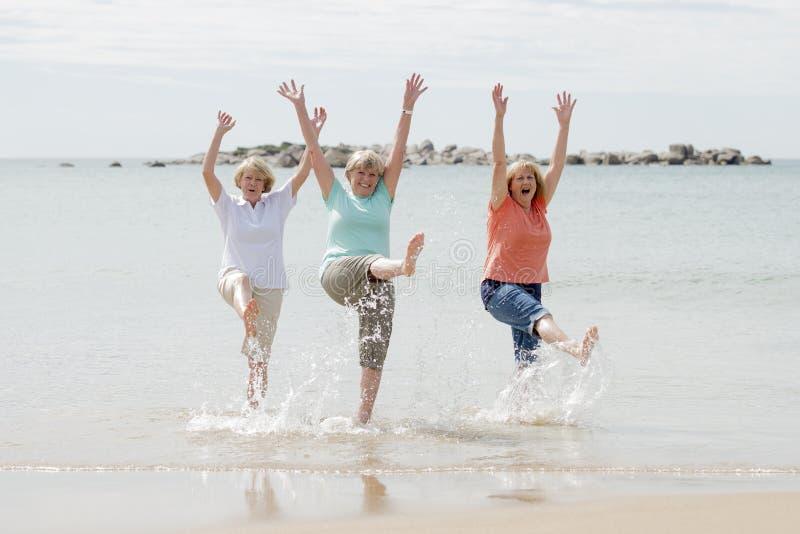 Gruppe von drei älteren reifen Frauen im Ruhestand auf ihrem 60s, das Spaß das glückliche Gehen auf dem Strandlächeln zusammen ge stockfotos