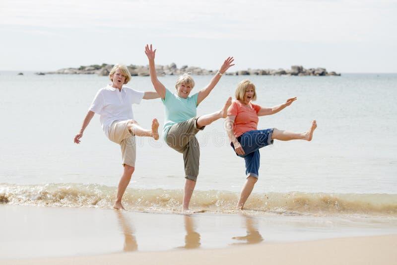 Gruppe von drei älteren reifen Frauen im Ruhestand auf ihrem 60s, das Spaß das glückliche Gehen auf dem Strandlächeln zusammen ge stockbild