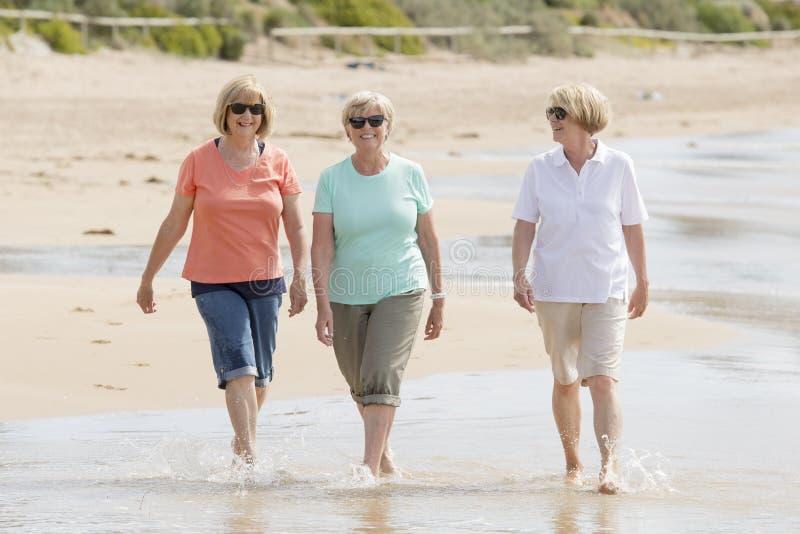Gruppe von drei älteren reifen Frauen im Ruhestand auf ihrem 60s, das Spaß das glückliche Gehen auf dem Strandlächeln zusammen ge stockfoto