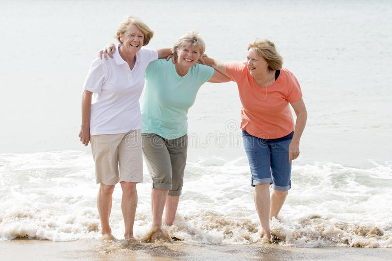 Gruppe von drei älteren reifen Frauen im Ruhestand auf ihrem 60s, das Spaß das glückliche Gehen auf dem Strandlächeln zusammen ge stockfotografie