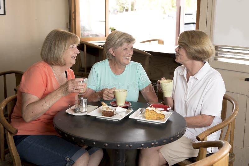 Gruppe von drei älteren reifen Frauenfreundinnen des reizenden Mittelalters, die für Kaffee und Tee mit Kuchen an der Kaffeestube stockfotografie