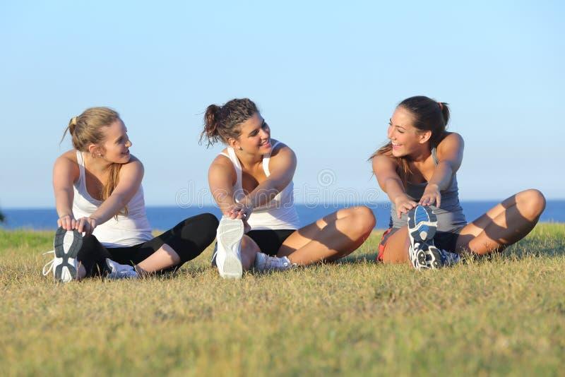 Gruppe von drei Frauen, die nach Sport ausdehnen stockfotos