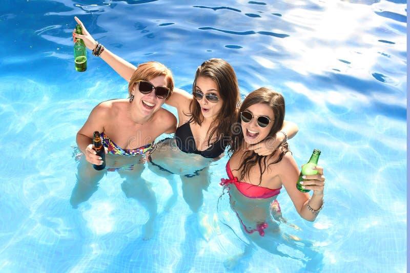 Gruppe von drei glücklichen Freundinnen, die Bad in Swimmingpool t haben stockfotos